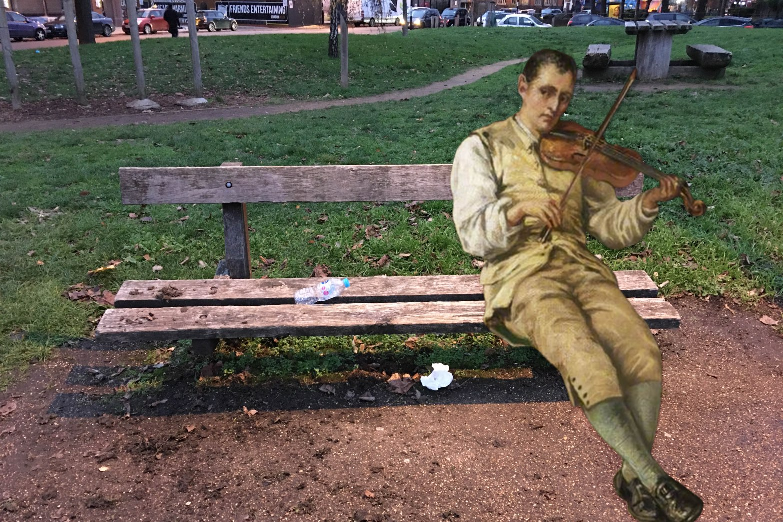 """Photograph of bench in Lower Pepys Park, Deptford, with a violin-playing figure from Alfred Walter Bayes's """"Samuel Crompton Inventing the Spinning Mule"""" (1880)"""