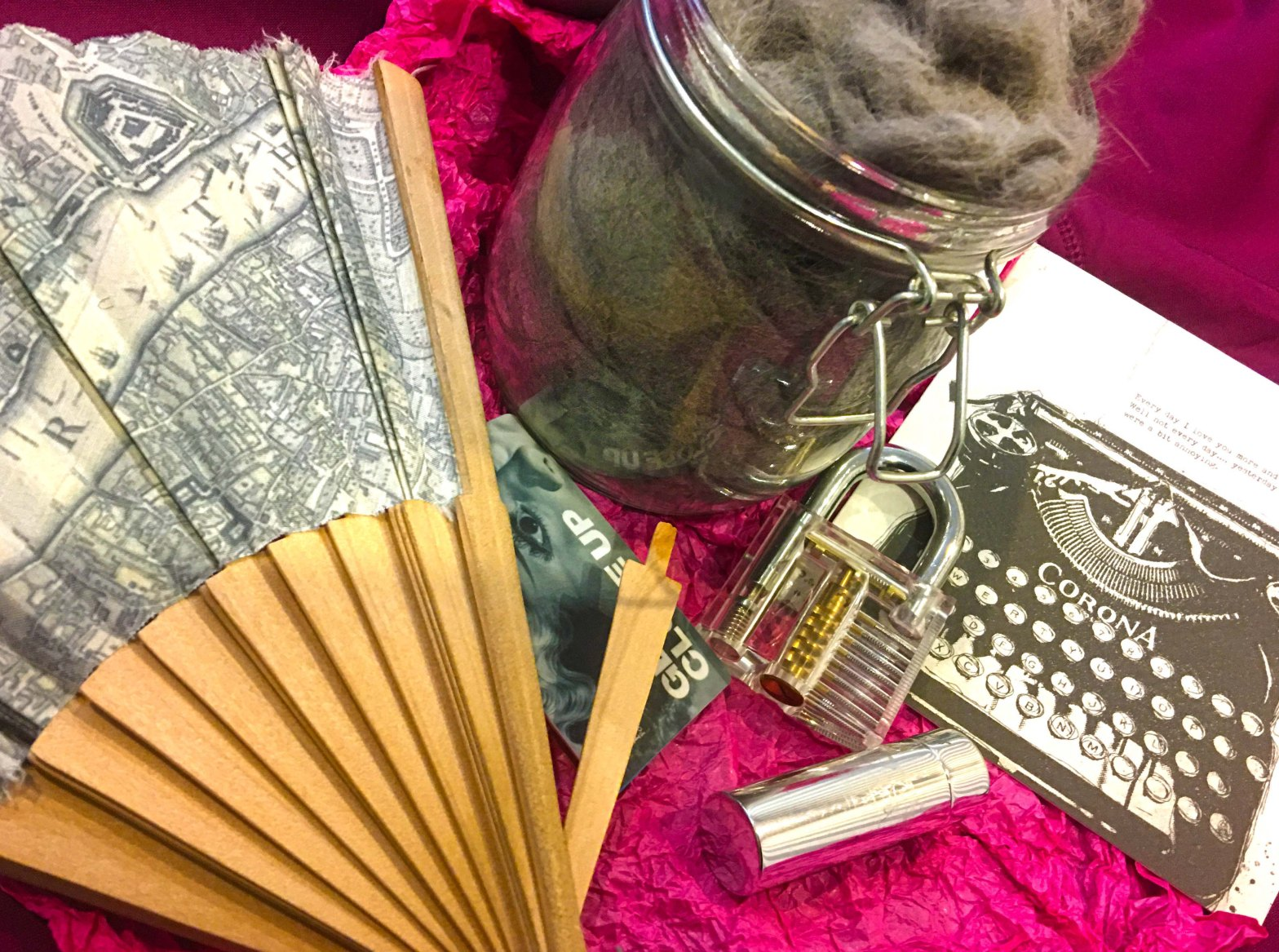 Photograph of various personal items: London map fan, lockpicking practice lock, lipstick, BFI membership card, card featuring Corona typewriter, and jar full of BlueBlue's cat fur.