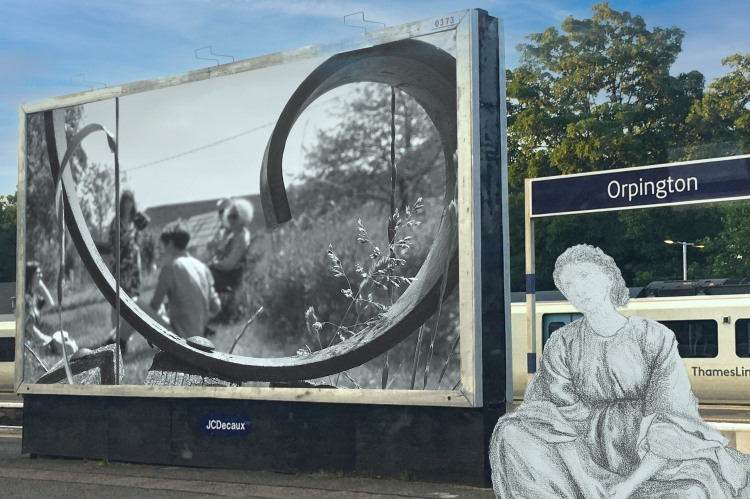 """Edward Burne-Jones's """"Green Summer Drapery Study of Central Figure"""" (1863–1864) on the platform at Orpington Station next to a billboard with a B&W photograph taken at Charleton Farm, Lewes, East Sussex on 12 June 2021"""