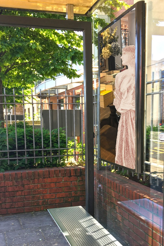 """Edward Burne-Jones's """"The Mirror of Venus – Study of Kneeling Female Attendant"""" (1865–66) next to a table of books at the Piccadilly Waterstones on the side of a bus shelter on Evelyn Street in Deptford"""